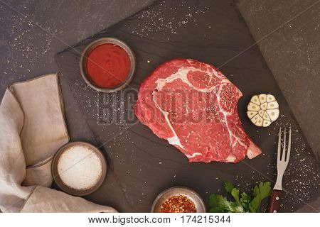 Fresh raw beef rib eye steak with seasoning, ready for grill. Top view, dark toned image