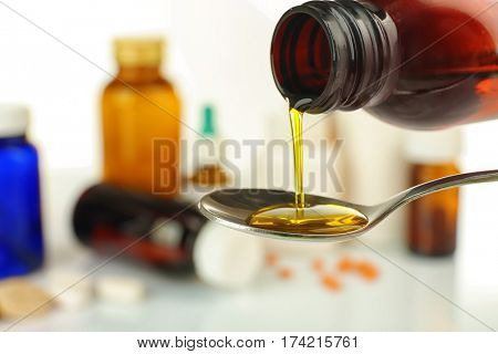 Pouring cough syrup into spoon on blurred background of medicines