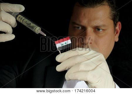 Young Businessman Gives A Financial Injection To Iraqi Flag Isolated On Black Background