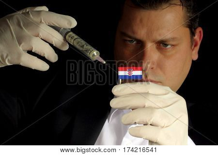Young Businessman Gives A Financial Injection To Croatian Flag Isolated On Black Background