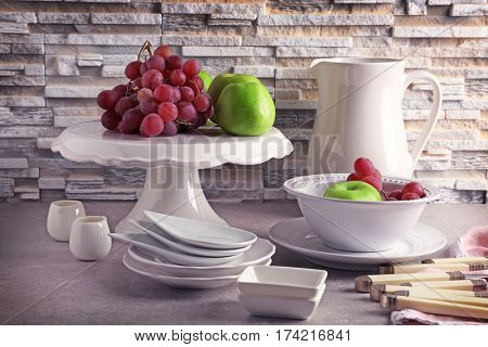 Composition with rustic dinnerware and fruits on light brick background