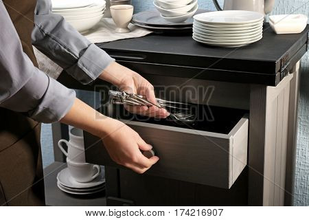 Woman putting silverware into drawer, closeup