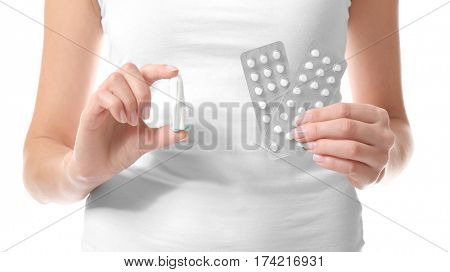 Close up view of woman holding tampon and pills, on white background. Gynecology concept