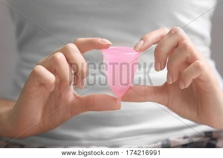 Close up view of young woman with menstrual cup. Gynecology concept