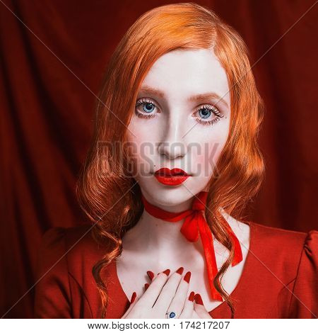 Close up portrait. A woman portrait with red curly hair in a red dress and retro makeup on a red background. Red-haired girl portrait with pale skin blue eyes a bright unusual appearance red lips and red ribbon around neck. Red magic portrait. Fashion por
