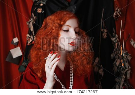 A woman smoke with red hair in a red fitting dress with a cigarette in her mouth. Red-haired girl with pale skin and blue eyes with a bright unusual appearance with beads around her neck smoke cigarette. Noir image