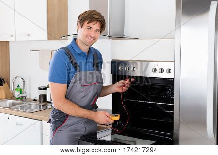 Young Male Technician Checking Oven With Digital Multimeter