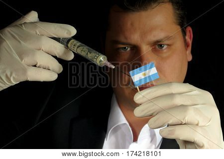 Young Businessman Gives A Financial Injection To Argentine Flag Isolated On Black Background