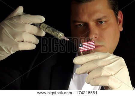 Young Businessman Gives A Financial Injection To Liberian Flag Isolated On Black Background