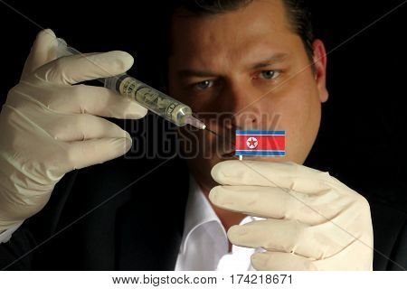Young Businessman Gives A Financial Injection To North Korean Flag Isolated On Black Background