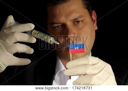 Young Businessman Gives A Financial Injection To Haitian Flag Isolated On Black Background