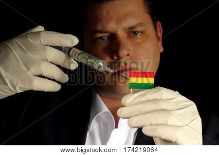 Young Businessman Gives A Financial Injection To Bolivian Flag Isolated On Black Background
