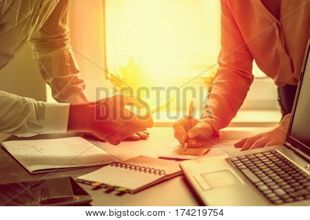 business couple working sunflare behind