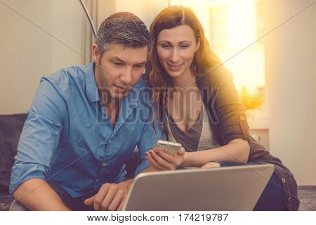 couple booking shopping online with smartphone and notebook