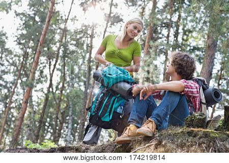 Young hiking couple looking at each other in forest