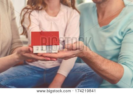 family with daughter hand holding home toy