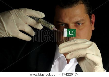Young Businessman Gives A Financial Injection To Pakistani Flag Isolated On Black Background