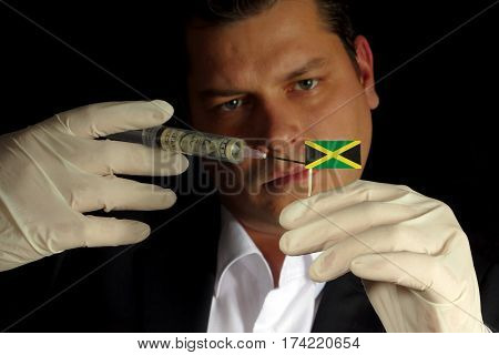 Young Businessman Gives A Financial Injection To Jamaican Flag Isolated On Black Background