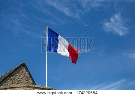 French flag fluttering in the wind on blue sky background