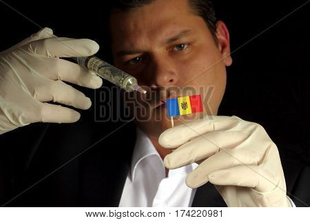 Young Businessman Gives A Financial Injection To Moldovan Flag Isolated On Black Background