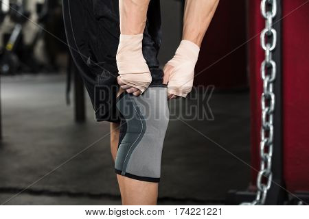 Close-up Of A Person Preparing For Training Wearing Knee Bandage In The Gym