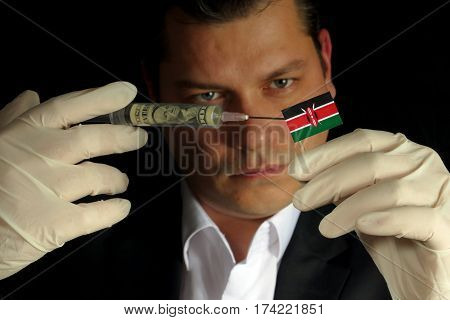 Young Businessman Gives A Financial Injection To Kenyan Flag Isolated On Black Background