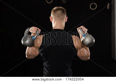Rear View Of A Young Athlete Man Doing Exercise With Kettle Bell In The Gym