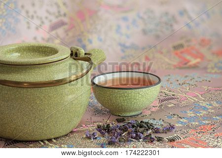 Kettle cup with tea background of traditional eastern pattern with pagodas