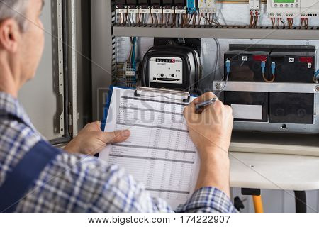 Close-up Of A Male Technician Writing Reading Of Meter On Clipboard