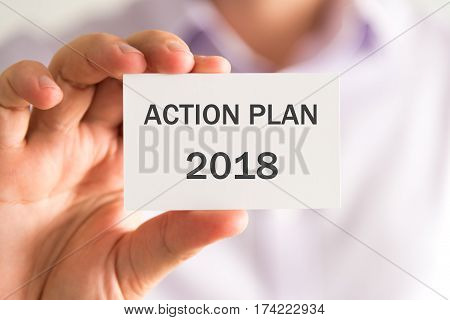 Businessman Holding A Card With Action Plan 2018 Message