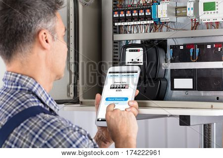 Close-up Of A Male Technician Doing Meter Reading Using Mobilephone