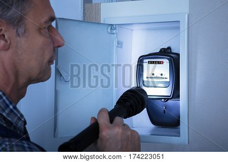 Close-up Of A Electrician Examining A Electricity Meter With A Torch