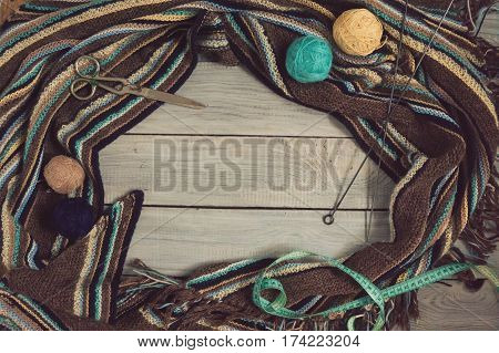 Fragment of handmade knitted fabric, knitting needles and balls of yarn on painted white boards