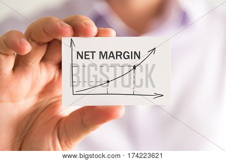 Businessman Holding A Card With Net Margin Rising Arrow And Chart