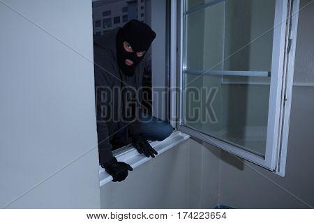 Burglar Wearing Balaclava Breaking Into A House Through The Window