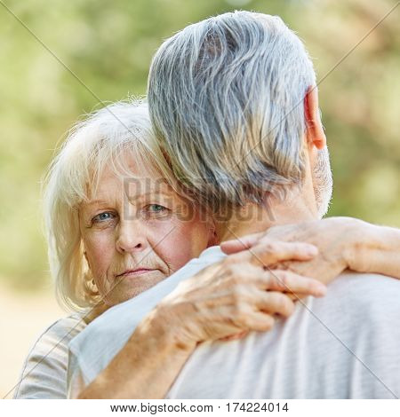 Seniors hugging each other in the nature in summer