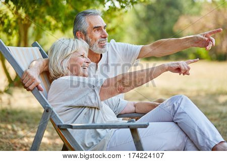 Senior couple happy in summer sitting on a deck chair