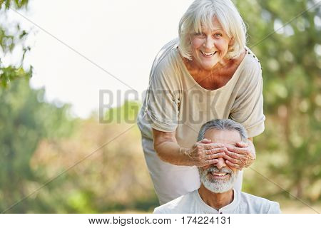 Senior woman covers her husband's eyes from the back in the nature