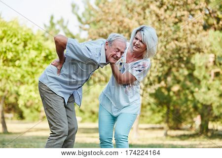 Woman helps old man with back pain in the park in summer