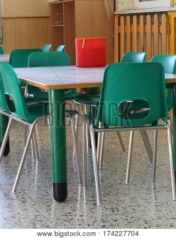inside of a school classroom with green chairs and no children