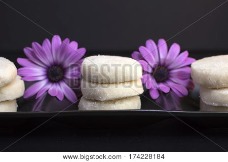 Lemon and Vanilla Shortbread Cookies Plated On Black Ceramic and Garnished with Purple Daisies