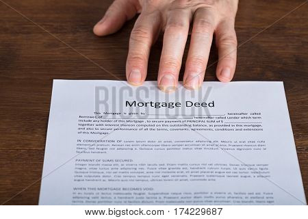 High Angle View Of A Person Hand Presents A Mortgage Document On Wooden Desk