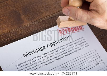 High Angle View Of An Approved Stamp On Mortgage Application Form At Wooden Desk