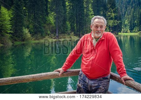 Portrait of a handsome senior man in bright sweater near the beautiful forest lake. Looking aside. Smiling happy senior man with gray hair and beard on excursion. Outdoors. Horizontal image.