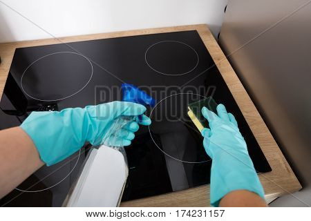 Close-up Of Person Hands Cleaning Induction Stove In Kitchen With Spray Bottle And Sponge