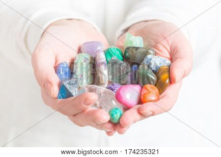 Multiple semi precious gemstones in hands