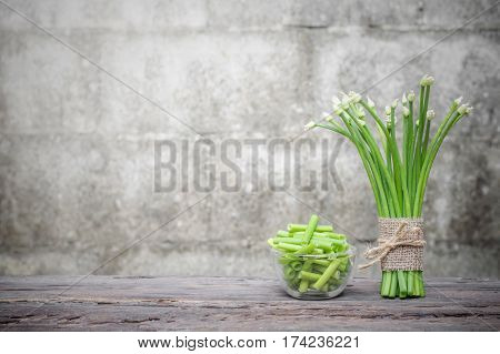 Chives flower or Chinese chives on wooden table and chives slice in glass bowl with old brick wall background