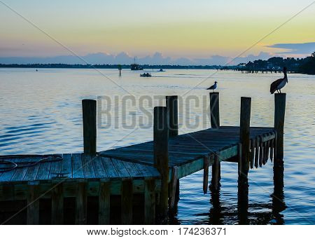 Waterscape of an inlet at dawn with boats heading to sea and birds silhouetted on a dock with reflections in the water