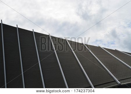 Curve roof of modern building against hazy cloud sky