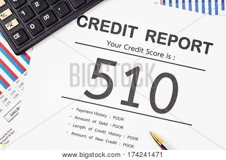 Credit score report with calculator and pen on business report document.